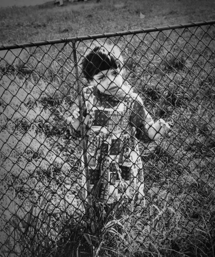 Girl peers through fence at orphanage in Romania - Ginger Wagoner, Photographer, Photosynthesis
